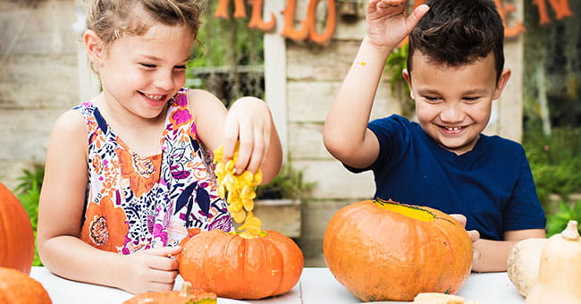 girl and boy carving pumpkins